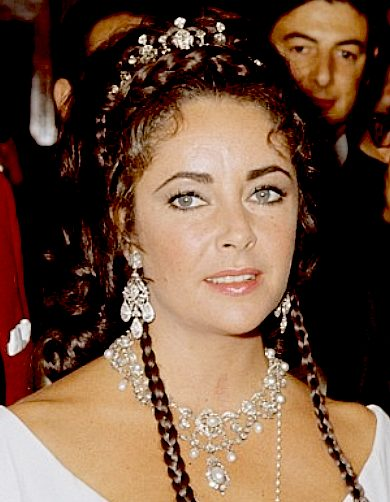 Liz Taylor wearing a diamond tiara and pearl necklace